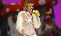 Miley Cyrus canta com seios amostra e microfone de banana